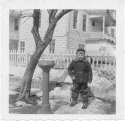 brother, Bruce next to water fountain in front of main house, winter 1956